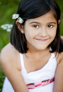 Outdoor portrait of cute little girl in green sunny meadow