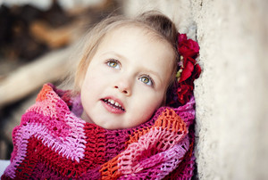 Outdoor portrait of cute little girl sitting and wrapped in the blanket