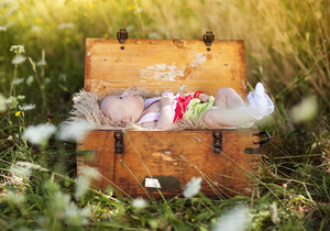Outdoor portrait of little baby girl lying down in old wooden suitcase
