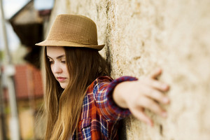 Outdoor portrait of teenage hipster girl in hat posing by the old wall