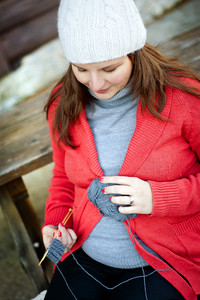 Outdoor winter portrait of pregnant woman knitting