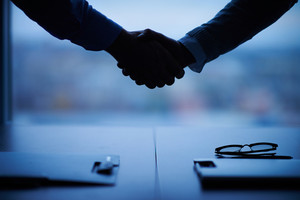 Outline of handshake of two businessmen over workplace