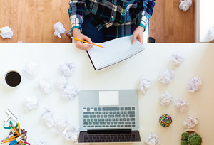 Overhead view of a young woman with crumpled paper creativity concept with notebook