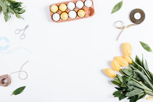 Painted eggs, tulips, rope, ribbon, scissors and place for text on a white background, top view