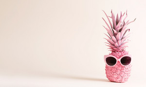 Painted pink pineapple with sunglasses on an off white bright background