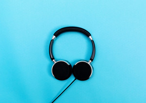 Pair of black headphones on a blue background