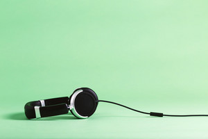 Pair of black headphones on a green background