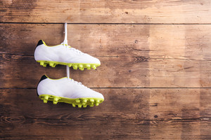 Pair of football shoes hang on a nail on a wooden fence background