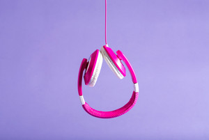 Pair of pink headphones on a purple background