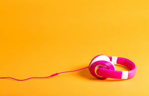 Pair of pink headphones on a yellow background