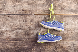 Pair of running shoes hang on a nail on a wooden fence background