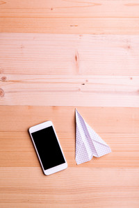 Paper airplane and smart phone against wooden background, empty copy space