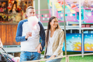 Parents with cotton candy at fun fair, holding and eating it, looking at their child taking ride, amusement park