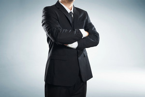 part of man body side folded his arms in black suit on white background; business concept