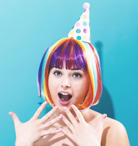 Party theme with a woman in a colorful wig on a blue background