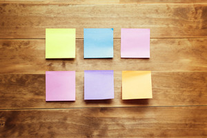Pastel sticky notes on a wood desk