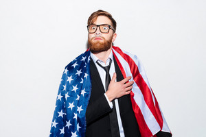 Patriotic business man in glases and suit with USA flag holding hand on heart and smeared in cocaine. Isolated gray background