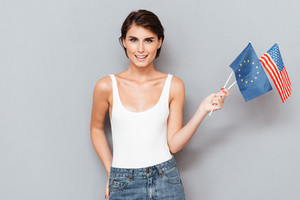 Patriotic happy woman holding european and usa flags over gray background
