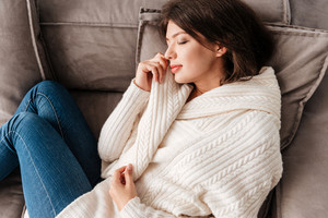 Peaceful cute young woman lying and sleeping on sofa
