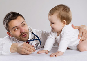 Pediatrician doctor is playing with little baby boy