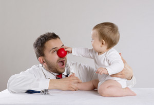 Pediatrician doctor with red nose showing baby stethoscope