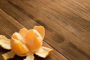 Peeled tangerine on a wooden table. Copy space.