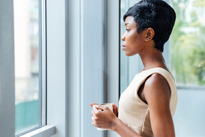 Pensive african american young businesswoman drinking coffee near the window in office