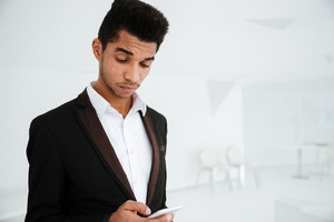 Pensive African business man in black suit writing message on phone in office