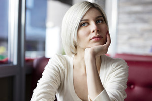 Pensive and thoughtful young woman at cafe