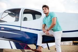 Pensive attrative young man pilot standing near small aircraft