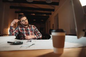 Pensive bearded man sitting at his working place with graphs and cup of coffee