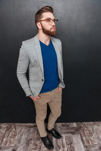 Pensive bearded young businessman standing and thinking