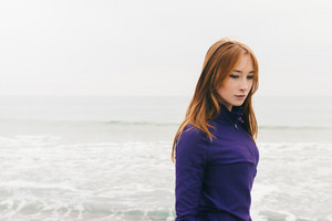 Pensive beautiful young red-haired girl on the beach on a cloudy day, copy space