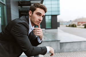 Pensive business man in suit standing outdoors near the office. Side view
