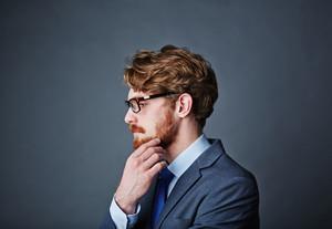 Pensive businessman touching his beard
