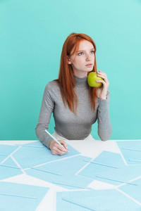 Pensive cute young woman holding apple and writing at the table over blue background