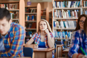 Pensive girl sitting at the desk at lesson in college