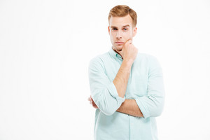 Pensive handsome young businessman stading with hands folded and thinking over white background