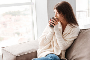 Pensive pretty young woman thinking and drinking coffee at home