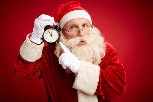 Pensive Santa Claus pointing at clock showing five minutes to midnight