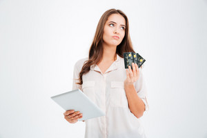 Pensive woman holding credit card and using tablet computer isolated on a white background