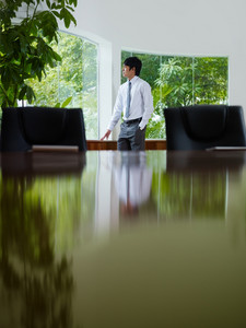 Pensive young asian business man looking out of the window in meeting room window. Side view, copy space