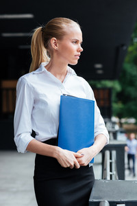 Pensive young business woman holding blue folder and looking away outdoors