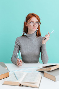 Pensive young woman in round glasses with pencils studying and thinking over blue background