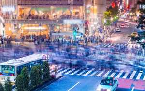 People and vehicles cross the famously busy Shibuya scramble intersection in Tokyo