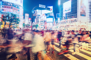 People and vehicles cross the famously busy Shibuya station intersection in Tokyo