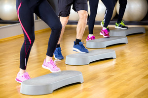 People training with step platform at fitness gym center