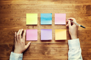Person organizing things with pastel sticky notes at a desk
