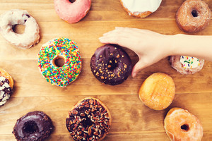 Person placing assorted colorful donuts on a wooden background