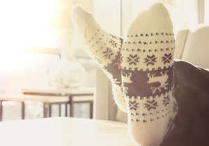 Person relaxing in Christmas themed socks indoors